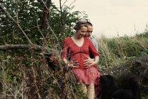 Pareja embarazada romántica sentada en el tronco del árbol - foto de stock