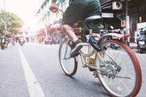 Waist down of young male hipster cycling along city street, Shanghai French Concession, Shanghai, China — Stock Photo