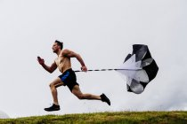 Man running and training with parachute — Stock Photo