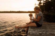 Mãe sentada no cais com a filha do bebê, salpicando os pés no lago — Fotografia de Stock