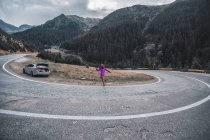 Young woman jumping on mountain road, Draja, Vaslui, Romania — Stock Photo