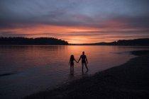 Silhuetas de casal na praia ao pôr do sol — Fotografia de Stock
