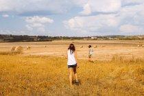 Rear view of women walking in wheat field — Stock Photo