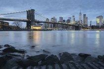 Cityscape with Brooklyn Bridge and Lower Manhattan skyline at dusk, New York, USA — Stock Photo