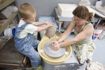 Mother and son working with clay in studio — Stock Photo