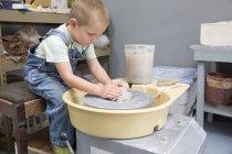 Мальчик формирует глину на гончарном круге — стоковое фото