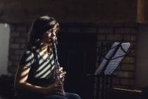 Girl with music stand playing on clarinet by fireplace — Stock Photo