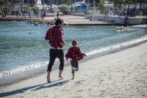Батько і син вздовж пляжу — стокове фото