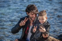 Father and son beside sea taking selfie — Stock Photo
