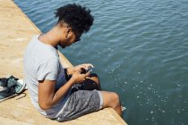 Man using mobile phone by edge of water — Stock Photo
