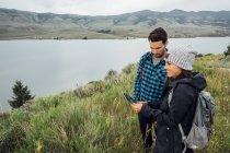Couple debout à côté du réservoir de Dillon, à l'aide de tablette numérique, Silverthorne, Colorado, é.-u. — Photo de stock