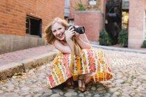 Молодая женщина-фотограф приседает с камерой на мощеной улице — стоковое фото