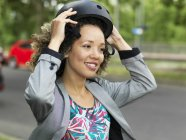 Mid adult woman putting on bicycle safety helmet — Stock Photo