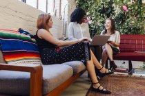 Коллеги сидят вместе на диване в офисе и используют ноутбук — стоковое фото