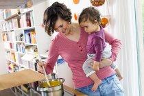 Матері проведення дівчинку під час приготування їжі на кухні — стокове фото