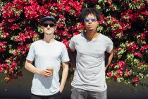Freunde Seite an Seite mit roten Bougainvilleen im Hintergrund — Stockfoto