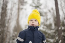 Boy in yellow knit hat in snow covered forest — Stock Photo