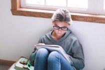 Chica sentada en el suelo y escribiendo la tarea - foto de stock