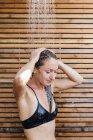 Giovane donna che lava i capelli nella doccia esterna — Foto stock