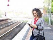 Середине взрослая женщина, стоя на железнодорожной платформе, с помощью смартфона, холдинг одноразовые кофе Кубок — стоковое фото