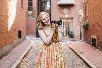 Молодая женщина-фотограф с камерой на мощеной улице — стоковое фото