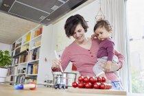 Матері, тримаючи дитину Дівчинка кухні під час приготування їжі — стокове фото