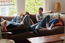 Three young women laughing on sofa in living room — Stock Photo