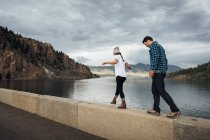 Couple walking along wall beside Dillon Reservoir, Silverthorne, Colorado, USA — Stock Photo