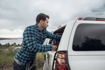 Mid adult man reaching into window of parked car, Silverthorne, Colorado, USA — Stock Photo