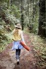 Mujer joven en trilby paseando en el bosque - foto de stock