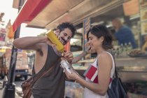 Happy tourist couple putting mustard on take away pretzel on street, Manhattan, New York, USA — Stock Photo