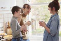 Amigos sosteniendo tazas de café y charlando en la cocina - foto de stock