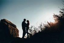 Vue en angle bas du couple romantique mi-adulte rétroéclairé sur la côte, oblast d'Odessa, Ukraine — Photo de stock