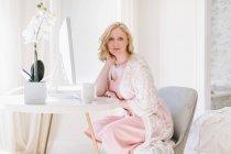 Молодая женщина сидит на столе в гостиной — стоковое фото