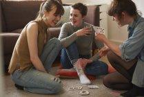 Amis jouant aux cartes dans le salon — Photo de stock