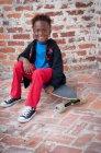 Portrait de jeune garçon assis sur une planche à roulettes — Photo de stock
