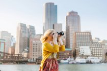 Молодая женщина фотографирует из причала, Бостон, Массачусетс, США — стоковое фото