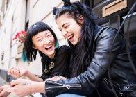 Due giovane donna elegante che ride sulla porta di casa — Foto stock