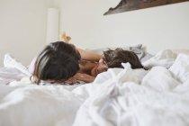 Мать и дочь лежат на кровати в светлой спальне — стоковое фото
