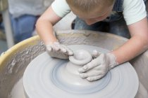 Boy shaping clay on potter wheel — Stock Photo