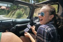 Young woman on road trip with boyfriend laughing at instant photograph, Breckenridge, Colorado, USA — Stock Photo