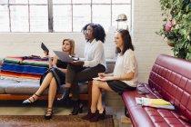 Seitenansicht von Kollegen, die mit Laptop zusammen auf dem Sofa im Büro sitzen — Stockfoto