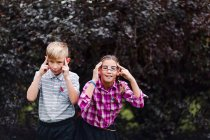 Siblings dressed up as nerds, hands on head looking at camera — Stock Photo