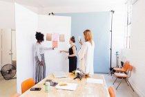 Коллеги в творческой студии обсуждают образцы — стоковое фото