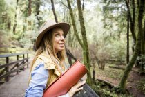 Young woman in trilby looking up from forest footbridge — Stock Photo