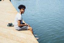 Молодой человек, сидящий на берегу воды — стоковое фото