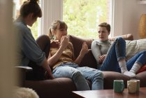 Три девушки болтают на диване — стоковое фото