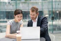 Бизнесмен и женщина смотрят на ноутбук в кафе на тротуаре — стоковое фото