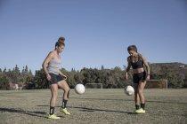 Duas mulheres em campo de futebol jogando futebol — Fotografia de Stock