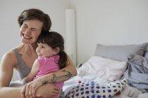 Мать и дочь обнимаются в светлой спальне — стоковое фото